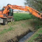 excavator digging a ditch with bucket attachment - herder