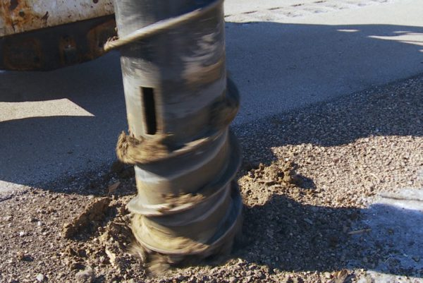 post removal in frozen ground drilling with hydraulic attachment for a skid steer